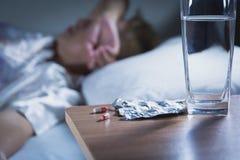 病的妇女在睡觉前采取胶囊药片和饮料水 免版税库存图片