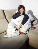 年轻病的妇女坐在鸭绒垫子和毯子包裹的长沙发感到凄惨 库存图片