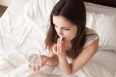 病的妇女饮用的药片在床上早晨 免版税图库摄影