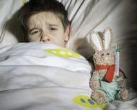 病的孩子在与玩具熊的床上 免版税库存照片