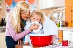 病的孩子的母亲关心有蒸气浴的 免版税库存照片