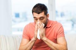 病的对纸巾的人吹的鼻子在家 免版税库存照片