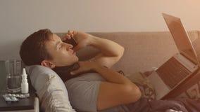 病的年轻人在床上运作在笔记本和谈话在电话 丰足药片和疗程在床头柜上 图库摄影