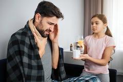 病的年轻人坐有他的女儿的沙发 人在喉头和头的举行手 严肃的小女孩看看他 她 库存图片