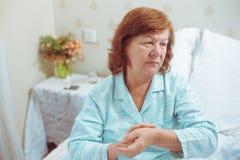 病的资深妇女在她的采取在她的手上的公寓的床上脉冲 免版税库存照片