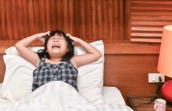 痒的女孩她的在床上的头发, 免版税库存照片