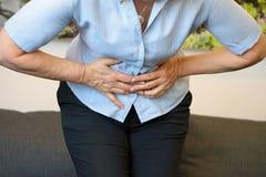 痛苦在一名年长妇女的腹部 免版税库存图片