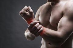 痛苦在手上 肌肉机体的男 摆在灰色背景的英俊的爱好健美者 免版税库存照片