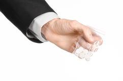 瘾和企业题目:在一套黑衣服的手在演播室拿着与白色药片的袋子在白色被隔绝的背景的一种药物 库存图片