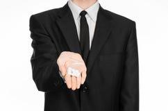 瘾和企业题目:在一套黑衣服的手在演播室拿着与白色药片的袋子在白色被隔绝的背景的一种药物 免版税库存照片