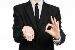 瘾和企业题目:在一套黑衣服的手在演播室拿着与白色药片的袋子在白色被隔绝的背景的一种药物 库存照片