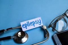 癫痫症题字有听诊器、镜片和智能手机看法在蓝色背景 免版税库存图片