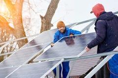 登上蓝色太阳模块的微笑的技术员在现代房子屋顶作为可选择能源的一个能承受的来源 库存照片