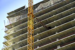 登上高层起重机到新的大厦的建筑 免版税库存图片