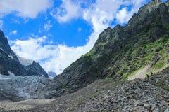 登上Ushba在Svaneti 佐治亚 森林围拢的山的斯诺伊上面 免版税库存照片