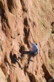 登山人下来面对形成rapelling的岩石 免版税图库摄影