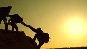 登山人剪影互相伸他们的手,上升在小山的上面 旅客以后上涨一 免版税图库摄影