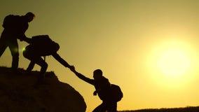 登山人剪影互相伸他们的手,上升在小山的上面 旅客以后上涨一 库存图片