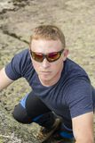 登山人在一个大岩石做上升的锻炼 免版税图库摄影