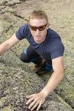 登山人在一个大岩石做上升的锻炼 库存照片