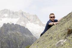 登山人在一个大岩石做上升的锻炼 免版税库存图片