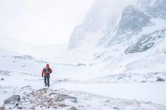 登山人在高山单独走在有风多雪的天气 免版税库存图片
