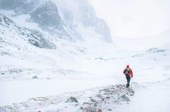登山人在高山单独走在有风多雪的天气 库存图片