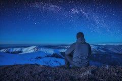 登山人坐地面在晚上 库存图片