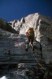 登山人坐式下降法的山顶 免版税库存图片