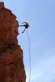 登山人坐式下降法的岩石 免版税图库摄影