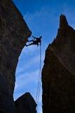 登山人坐式下降法的岩石 库存照片