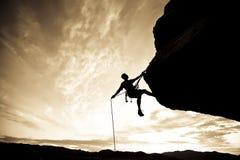 登山人坐式下降法的岩石 免版税库存图片