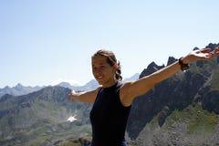 登山人女孩愉快的山顶层 免版税图库摄影