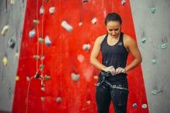 登山人妇女在人为岩石墙壁上把实践的系住的鞔具放 库存图片