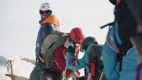 登山人帮助他的朋友并且紧固到他的马枪并且检查登上 整个小组准备下降 股票录像