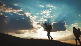 登山人帮助的队友攀登,有背包的人提供了援助一个帮手给他的朋友 徒步旅行者帮助的朋友 影视素材