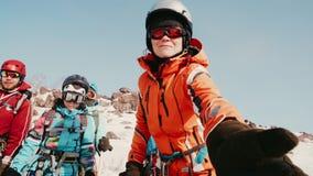 登山人被协调的队休假在一座多雪的山顶部,其中一个登山人为一杯热的茶到达 影视素材