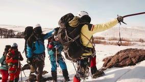 登山人队在一座大山的一个陡峭和多雪的倾斜做中止,检查您的路线 他们的领导展示 股票视频