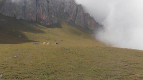 登山人阵营的空中射击山的在云彩中 股票录像