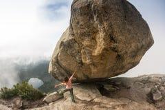 登山人bouldering本质上 在一块大石头的女孩攀登 做体育的妇女户外 运动员参与活动 库存图片