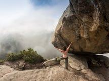 登山人bouldering本质上 在一块大石头的女孩攀登 做体育的妇女户外 运动员参与活动 库存照片