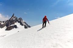 登山家伸手可及的距离山顶方式 免版税库存图片