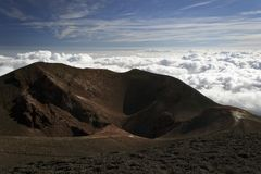 登山家圆的绝种火山口和剪影在云彩的在Etna火山顶部 免版税库存照片