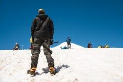 登山家站立与他的后面并且看山,并且一个人怎么学会沿雪倾斜滑和 免版税库存照片