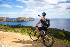 登山车的一个年轻人在西班牙落后并且拍在一个白色电话的一张照片在背景中地中海 免版税库存照片