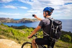 登山车的一个年轻人在西班牙落后并且拍在一个白色电话的一张照片在背景中地中海 图库摄影