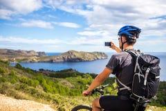 登山车的一个年轻人在西班牙落后并且拍在一个白色电话的一张照片在背景中地中海 免版税库存图片