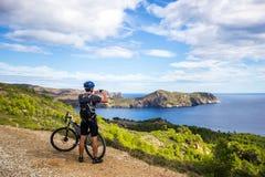 登山车的一个年轻人在西班牙落后并且拍在一个白色电话的一张照片在背景中地中海 库存图片
