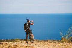 登山车的一个年轻人被停下来在地中海附近喝从一个瓶子的水在一条石路在西班牙 免版税库存照片