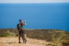 登山车的一个年轻人被停下来在地中海附近喝从一个瓶子的水在一条石路在西班牙 库存照片